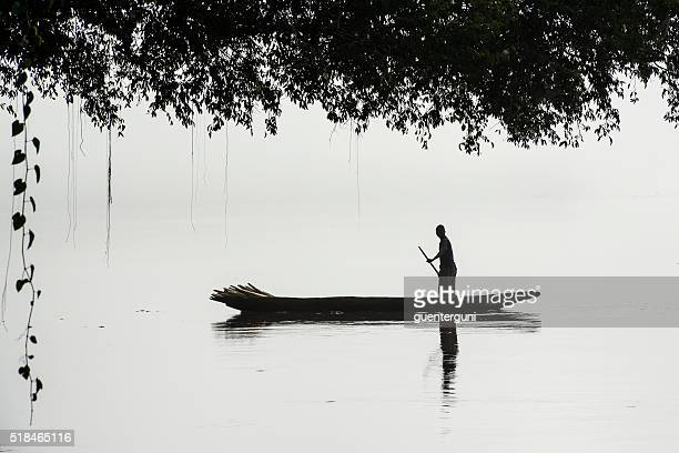 fisherman in a pirogue on the foggy congo river - dugout canoe stock photos and pictures