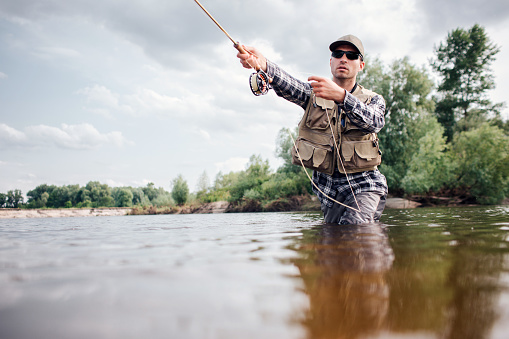 Fisherman in action. Guy is throwing spoon of fly rod in water and holding part of it in hand. He looks straight forward. Man wears special protection clothes. 1146124717