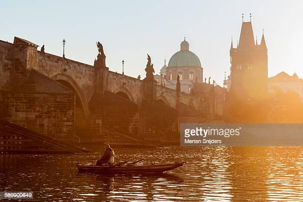 fisherman in boat below charles bridge - merten snijders stock-fotos und bilder