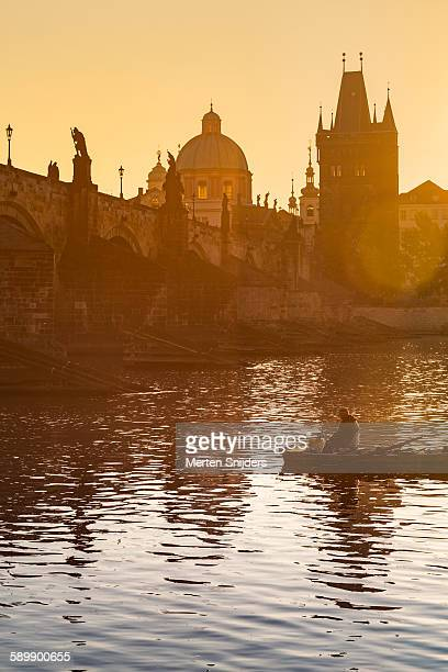 fisherman in boat below charles bridge - merten snijders 個照片及圖片檔