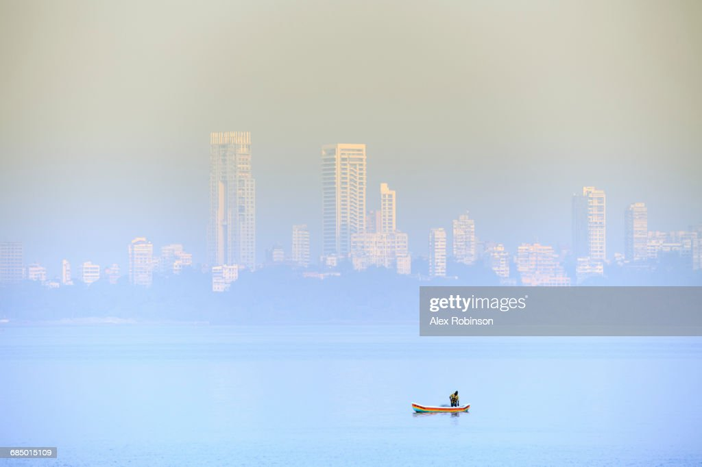 A fisherman in front of the skyscrapers of the Malabar Hills in Mumbai (Bombay), Maharashtra, India, Asia : Stock Photo