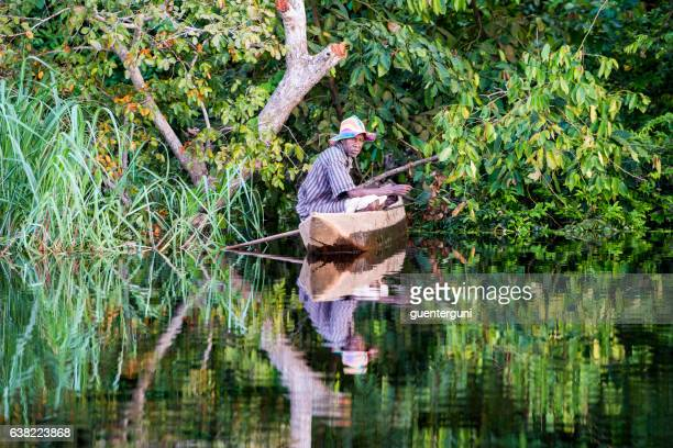 fisherman in his pirogue on congo river - democratic republic of the congo stock photos and pictures