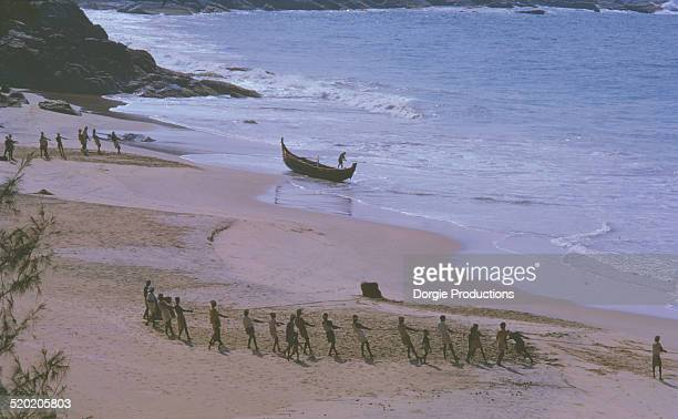 Fisherman in Kerala hauling in nets on the beach