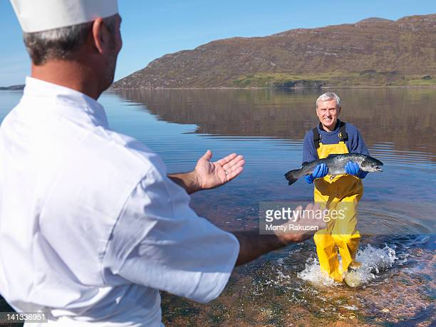 Fisherman in loch giving freshly caught salmon to chef