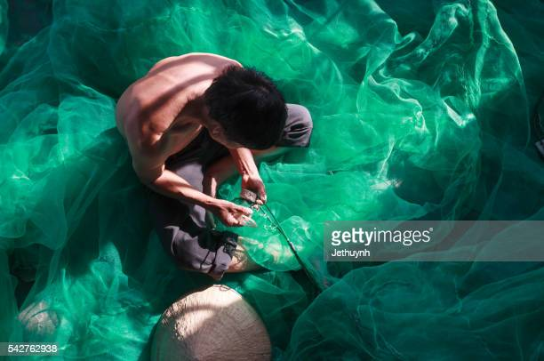 Fisherman in mending fishing net