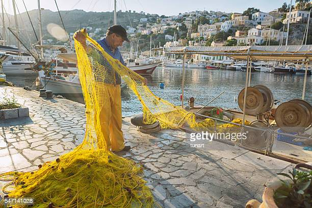 fisherman in symi harbour - symi stock photos and pictures