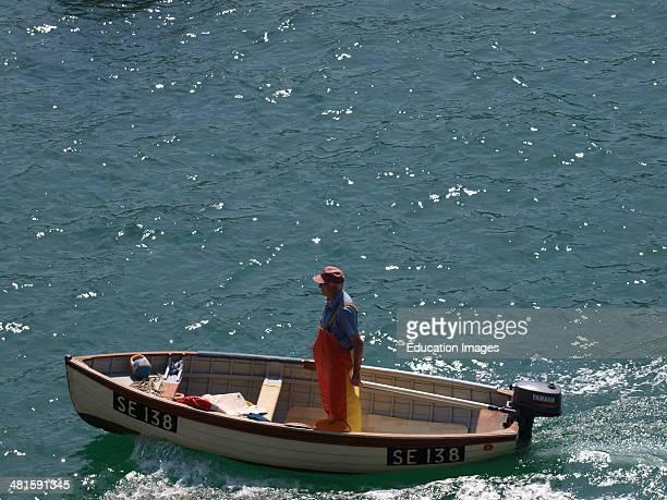 Fisherman in tender, Salcombe, Devon, UK.
