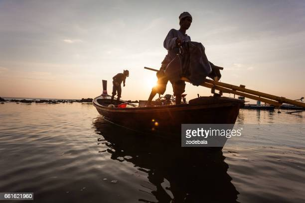 fisherman in thailand at sunset - thailandia stock photos and pictures