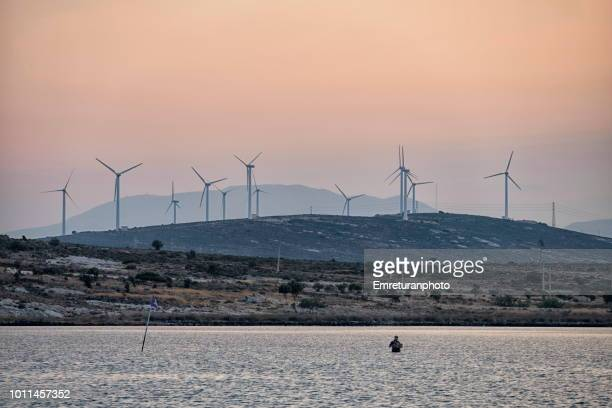 fisherman in waiders with windturbines at the background at dawn. - emreturanphoto stock pictures, royalty-free photos & images