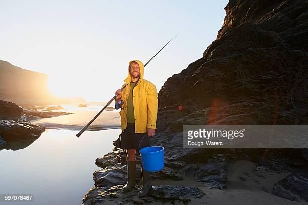 fisherman in yellow coat on rocky coast. - formação rochosa imagens e fotografias de stock