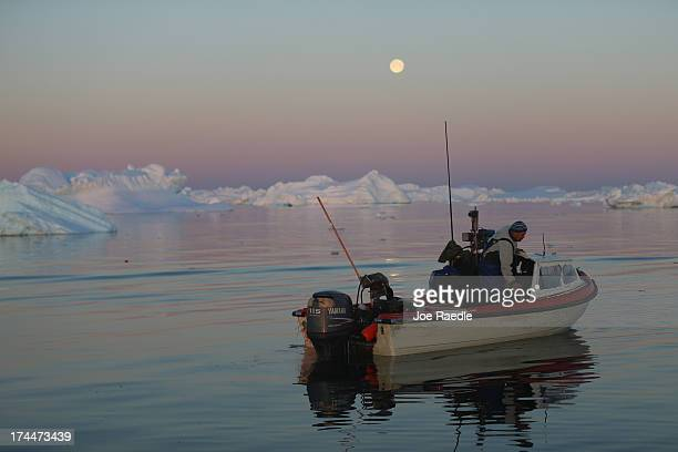 Fisherman Inunnguaq Petersen waits for fish to catch on the line he put out near icebergs that broke off from the Jakobshavn Glacier on July 23 2013...