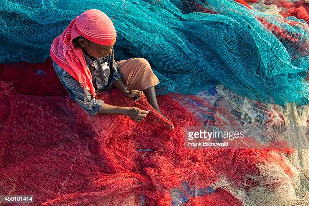 A fisherman is repairing red and blue fishing nets on the beach