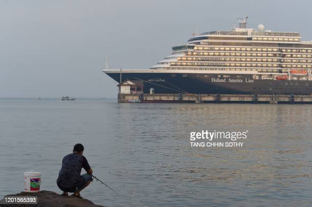 A fisherman is seen against the Westerdam cruise ship in Sihanoukville on February 18 where the liner on February 13 docked after being refused entry...