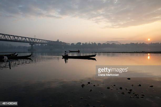 A fisherman is seen at sunset on Irrawaddy River on December 29 2013 in Kachin State Myanmar The Irrawaddy River is the lifeline of Burma running...