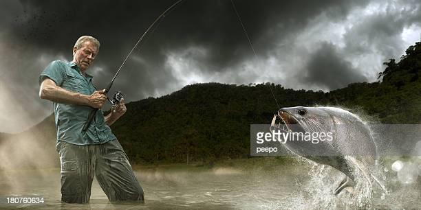 fisherman lands dangerous payara fish in amazon - vangen stockfoto's en -beelden
