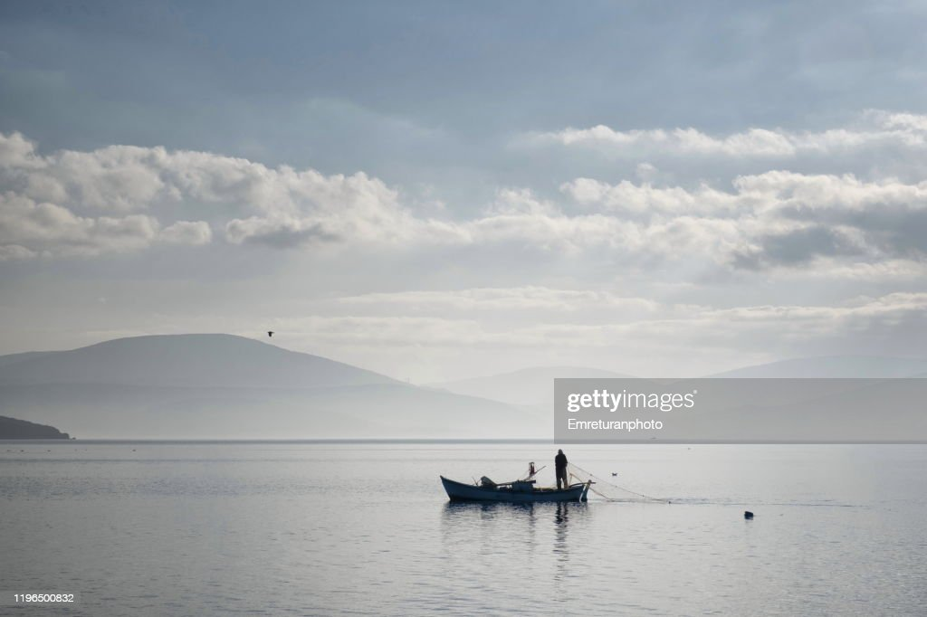 Fisherman laying net near Ozbek village on a very tranquil day. : Stock Photo