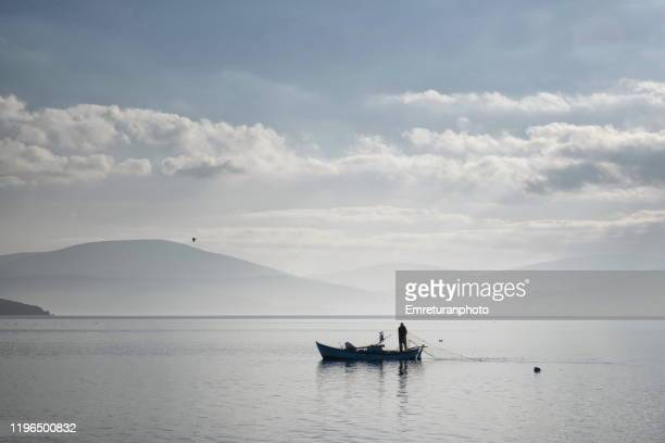 fisherman laying net near ozbek village on a very tranquil day. - emreturanphoto stock pictures, royalty-free photos & images