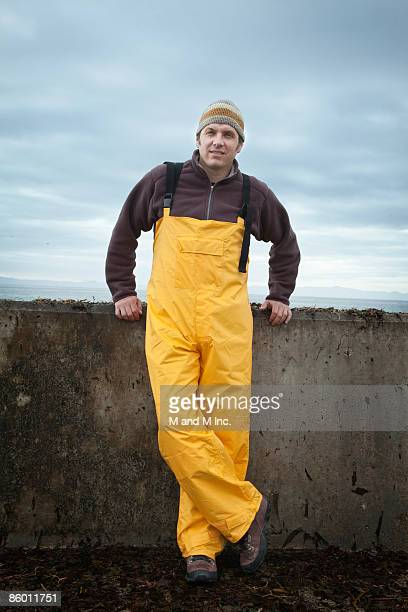 fisherman leaning against sea wall - fisherman stock pictures, royalty-free photos & images