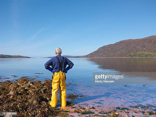 fisherman looking out to sea over loch, rear view - hand on hip stock pictures, royalty-free photos & images