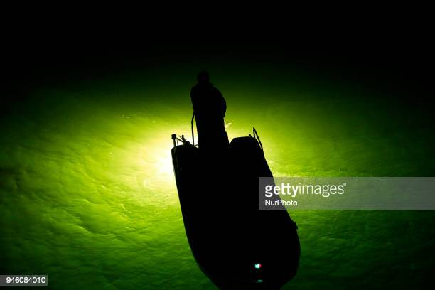 A fisherman looks for glass eels from their boats with the light of fish lamps reflecting on the surface of the water in the estuary of the Yoshino...