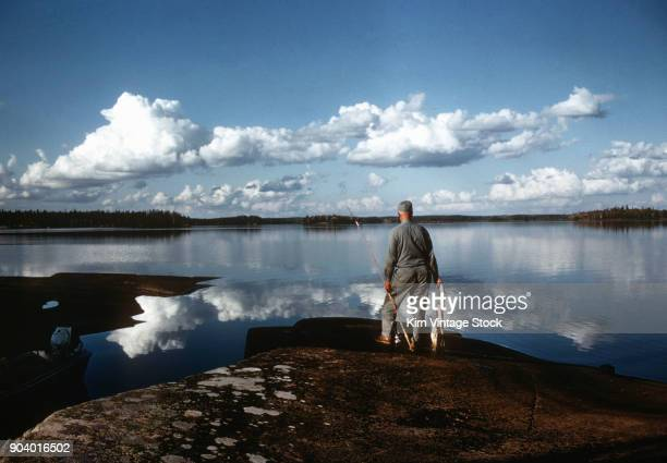 Fisherman looks out over the water after a successful day of fishing in Canada, ca. 1950.