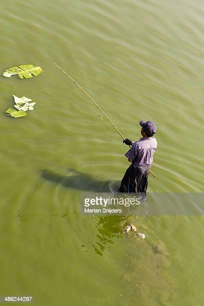 fisherman maneuvering through water with rod - merten snijders imagens e fotografias de stock
