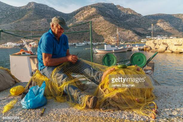 Fisherman, mending his nets on the quayside of Kamares Harbour, Sifnos, Cyclades Islands, Greece