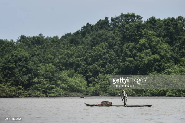 A fisherman navegates his canoe along the shore of the Pacific Ocean near Buenaventura in western Colombia on November 5 2018
