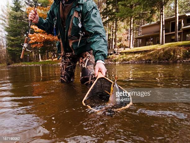 Fisherman Nets a Trout