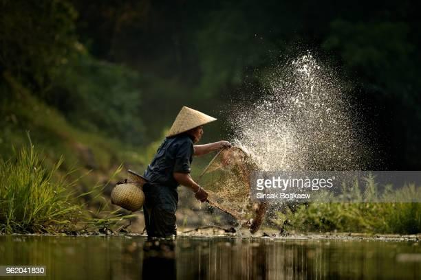 fisherman of lake in action - tradition stock-fotos und bilder