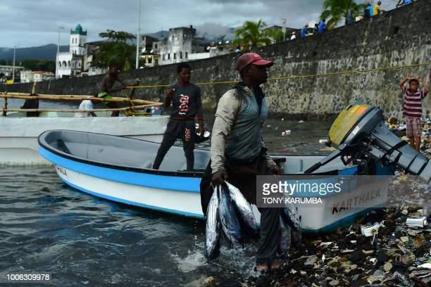 A fisherman offloads his catch of Tuna fish at a landing close to the port at Moroni on July 27 2018 where an upcoming referendum has caused...