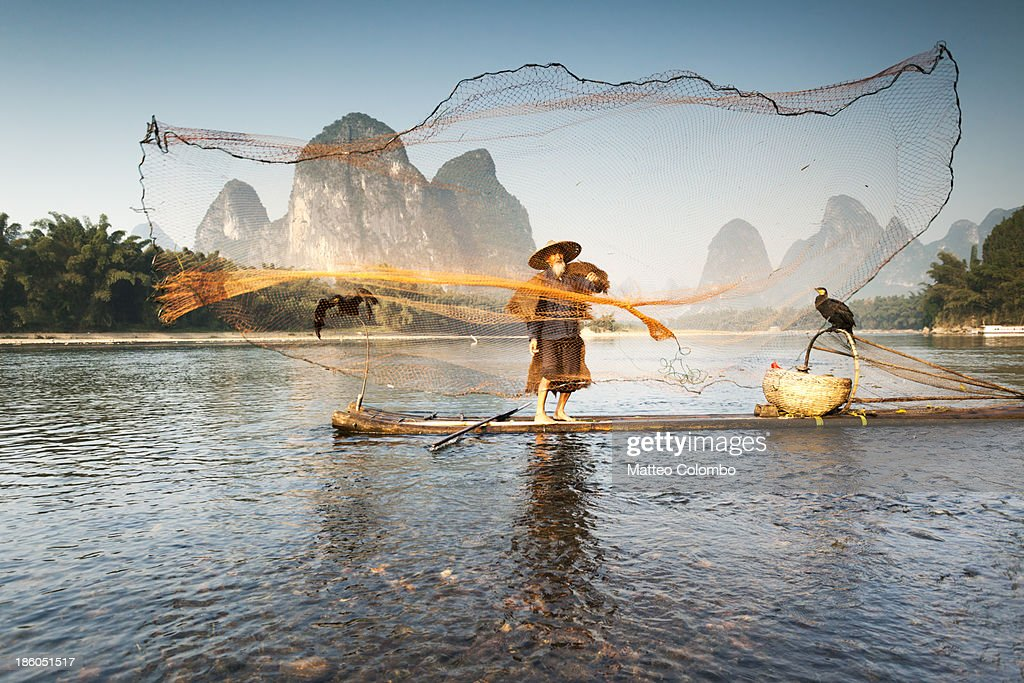 Fisherman on bamboo boat throwing the net : Stock Photo