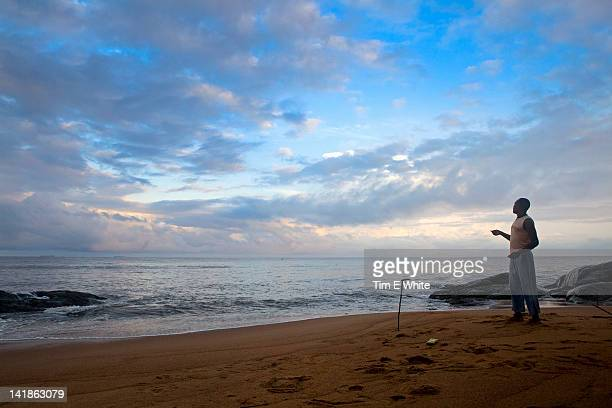 Fisherman on beach at sunrise, near Kribi, Cameroon, Africa