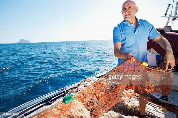 Fisherman on boat pulling in nets
