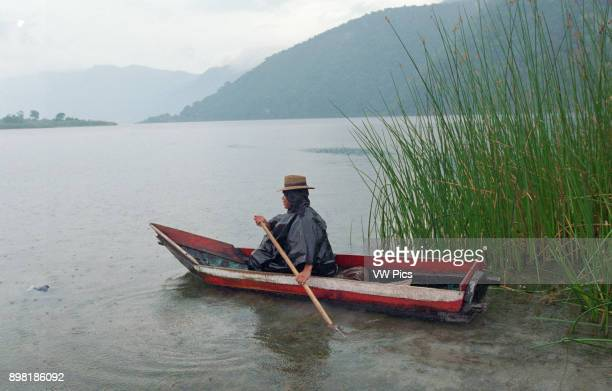 A fisherman on Lake Atitlan or Lago de Atitlan is surrounded by three volcanos in the Guatemalan Highlands of the Sierra Madre mountain range The...