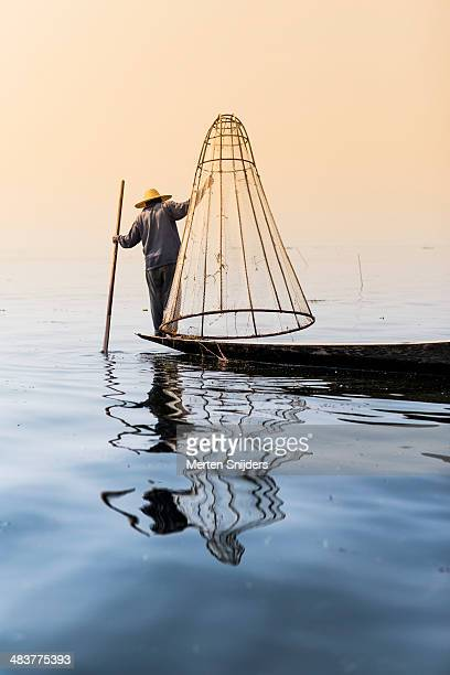 fisherman on lake lifting cone shaped net - merten snijders stock pictures, royalty-free photos & images