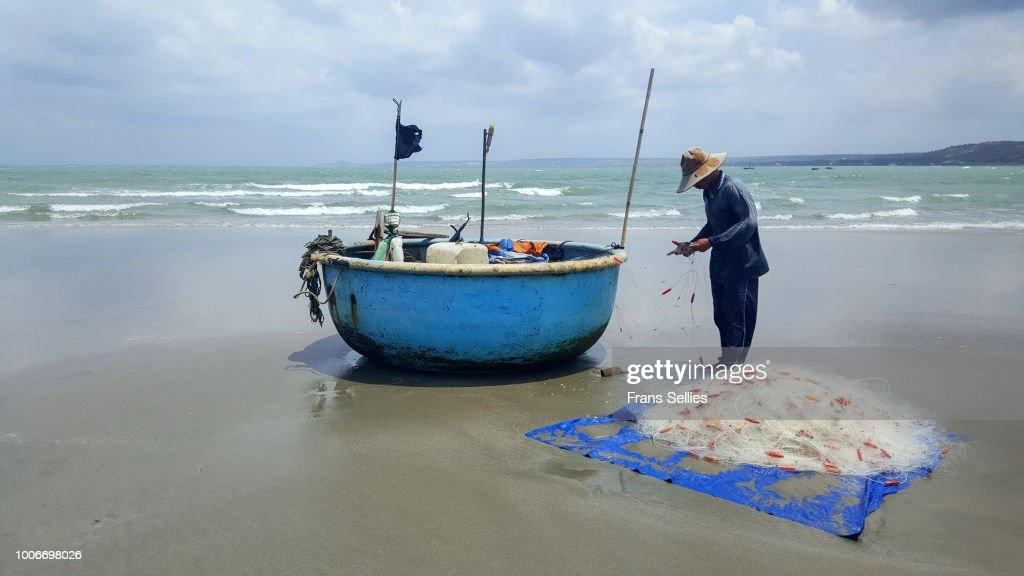 A fisherman on the beach of Mui né, Vietnam : Stockfoto