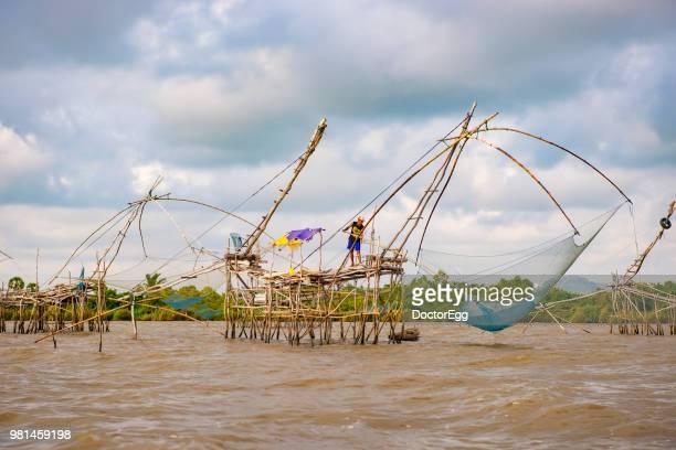 Fisherman on the Huge Fishing Net in Songkhla Lake, Pak Pra Fisherman Village, Southern of Thailand
