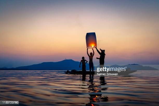 fisherman on wooden boat with floating lamp. - bougie espoir photos et images de collection