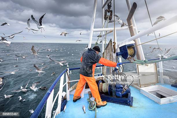 fisherman operating winch on deck of trawler - fishing industry stock pictures, royalty-free photos & images