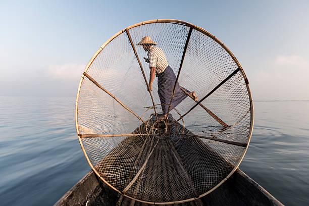 Fisherman paddles boat at Inle lake