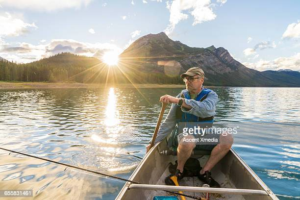 Fisherman paddles canoe across tranquil mtn lake