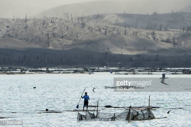 A fisherman paddles his makeshift boat made from bamboo at the foot of a mountain covered in mud and ash due to the eruption of the nearby Taal...