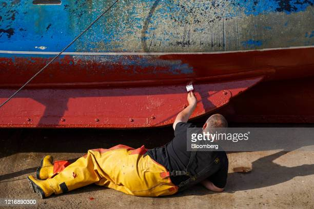 A fisherman paints the hull of his boat in the harbour in Scarborough UK on Tuesday June 2 2020 The threat of a nodeal Brexit is back and with it the...