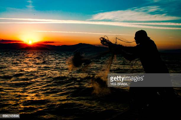 Fisherman playing fishing net during a sunset on the beach