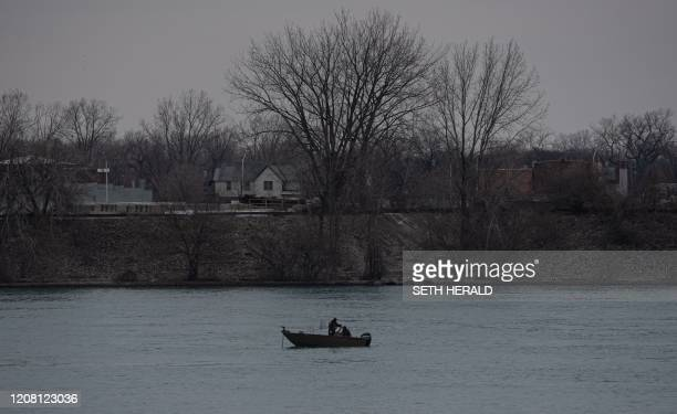 Fisherman practices social distancing on the Detroit River March 24,2020. - Tuesday morning March 2020 at 12:01am the state of Michigan went into a...