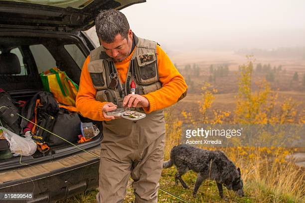 fisherman prepares box of flies before heading out - fishing tackle stock pictures, royalty-free photos & images