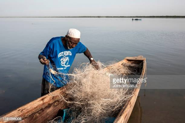 Fisherman prepares his fishing nets along the banks of the Casamance River in Ziguinchor on February 11, 2021.