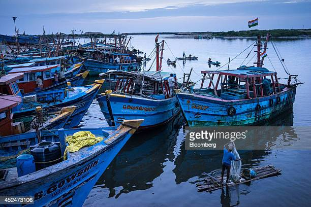 A fisherman prepares to cast his net as he sails next to fishing boats docked in the harbor in Puducherry India on Saturday July 19 2014 Indias gross...