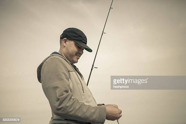 fisherman preparing fishing rod, truro, massachusetts, cape cod, usa - heshphoto stock pictures, royalty-free photos & images